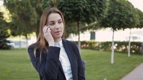 Ritratto della donna di affari che fa una telefonata all'aperto archivi video