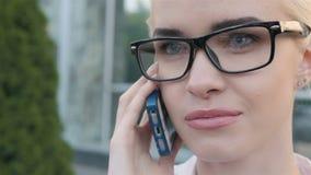Ritratto della donna di affari che fa una telefonata fuori del centro di affari stock footage