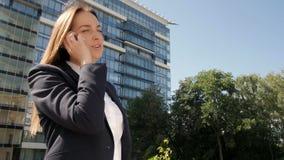 Ritratto della donna di affari che fa una telefonata fuori del centro di affari archivi video