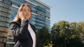 Ritratto della donna di affari che fa una telefonata fuori del centro di affari video d archivio