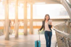 Ritratto della donna di affari che sembra compressa digitale con la borsa blu di viaggio sul passaggio pedonale Tono d'annata fotografia stock libera da diritti