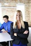 Ritratto della donna di affari che sorride con l'uomo di affari che lavora nell'ufficio moderno del mattone urbano Fotografie Stock Libere da Diritti