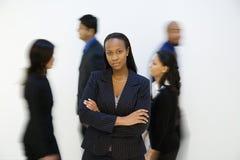 Ritratto della donna di affari con altri. camminare vicino. Immagine Stock