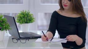 Ritratto della donna di affari con il blocco note ed il computer portatile sulla tavola nella sala