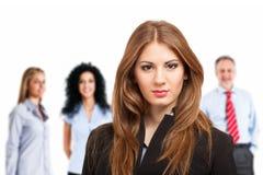Ritratto della donna di affari davanti al suo gruppo immagine stock
