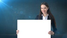 Ritratto della donna di affari di sorriso con il bordo bianco in bianco sul blu isolato Modello femminile con capelli lunghi Fotografia Stock Libera da Diritti