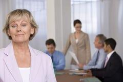 Ritratto della donna di affari e dei suoi colleghi. immagine stock libera da diritti