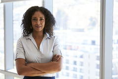 Ritratto della donna di affari Standing By Window in ufficio fotografia stock