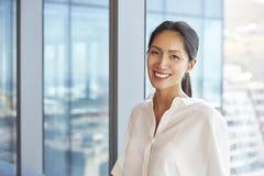 Ritratto della donna di affari Standing By Window in ufficio fotografie stock libere da diritti