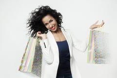 Ritratto della donna di colore soddisfatto dei sacchi di carta perfetti di acquisto, fronte sorridente Fotografia Stock