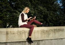 Ritratto della donna di estate La ragazza sta sedendosi fuori di un ufficio e sta tenendo una compressa Femmina con il taccuino Immagine Stock