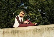 Ritratto della donna di estate La ragazza sta sedendosi fuori di un ufficio e sta tenendo una compressa Femmina con il taccuino Immagine Stock Libera da Diritti