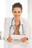 Ritratto della donna di medico che per mezzo del pc della compressa Fotografie Stock