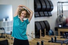 Ritratto della donna di misura che esegue allungando esercizio Fotografia Stock Libera da Diritti