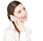 Ritratto della donna felice che chiama dal cellulare in camicia bianca Fotografia Stock