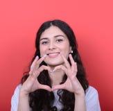 Ritratto della donna felice che fa forma del cuore con le mani contro il Re Fotografie Stock