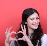 Ritratto della donna felice che fa forma del cuore con le mani contro il Re Immagini Stock