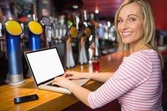 Ritratto della donna felice che per mezzo del computer portatile Fotografia Stock