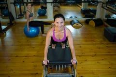 Ritratto della donna felice che pratica allungando esercizio sul riformatore Immagini Stock Libere da Diritti