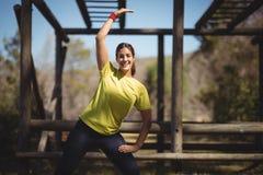Ritratto della donna felice che si esercita durante la corsa ad ostacoli Fotografia Stock