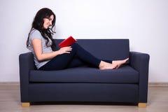 Ritratto della donna felice che si siede sul sofà e sul libro di lettura a casa Immagini Stock