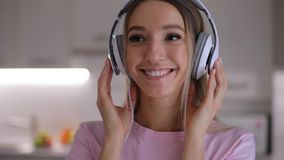 Ritratto della donna felice chegode dell'ascoltare la musica in cuffie a casa video d archivio