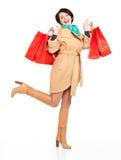 Ritratto della donna felice con i sacchetti della spesa in cappotto di autunno Fotografia Stock