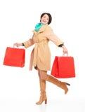 Ritratto della donna felice con le borse di acquisto in cappotto di autunno Immagini Stock