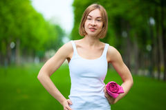Ritratto della donna felice di forma fisica con la stuoia di yoga all'aperto Immagini Stock