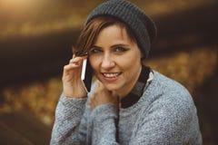Ritratto della donna felice e sorridente che si siede da solo nella foresta con lo smartphone Ragazza di Millenial che parla sul  Fotografie Stock