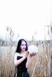 Ritratto della donna gotica con il cranio in un'alta erba Fotografie Stock Libere da Diritti