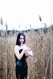 Ritratto della donna gotica con il cranio in un'alta erba Fotografia Stock