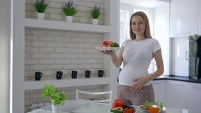Ritratto della donna in grande aspettativa felice con il grande piatto della vitamina della tenuta della pancia con i frutti util stock footage