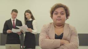 Ritratto della donna grassottella nell'usura convenzionale che guarda nella macchina fotografica nella priorità alta nell'ufficio archivi video