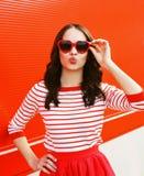 Ritratto della donna graziosa in occhiali da sole rossi che soffiano le labbra Immagine Stock