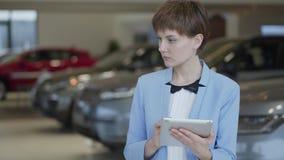 Ritratto della donna graziosa sicura nell'usura convenzionale facendo uso dei suoi supporti della compressa davanti alle automobi stock footage