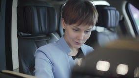 Ritratto della donna graziosa soddisfatta sorridente nel vestito blu di usura convenzionale che si siede dentro l'automobile nel  archivi video