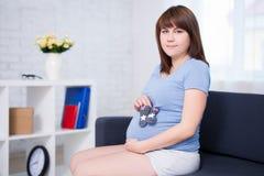 Ritratto della donna incinta che posa con i piccoli calzini Fotografia Stock Libera da Diritti