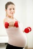 Ritratto della donna incinta che si esercita con le teste di legno Fotografie Stock