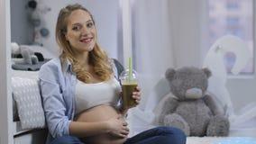 Ritratto della donna incinta che sorride con il frullato archivi video