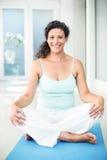 Ritratto della donna incinta felice che si siede sulla stuoia di esercizio Fotografia Stock