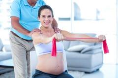 Ritratto della donna incinta sorridente che allunga la banda di esercizio Immagine Stock Libera da Diritti