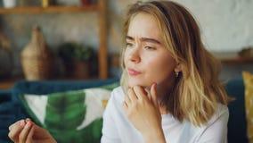 Ritratto della donna infelice che esamina anello di fidanzamento, toccando il suoi fronte e seduta sospirante da solo a casa coni archivi video