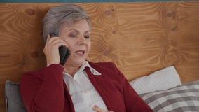 Ritratto della donna matura che si trova sul letto e che parla sullo smartphone archivi video