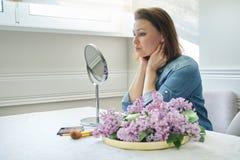 Ritratto della donna matura con lo specchio di trucco che massaggia il suoi fronte e collo, bei 40 anni femminili immagini stock libere da diritti