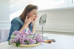 Ritratto della donna matura con lo specchio di trucco che massaggia il suoi fronte e collo, bei 40 anni femminili fotografie stock