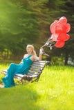 Ritratto della donna Mezzo Invecchiare che si siede sul banco fotografia stock