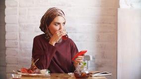 Ritratto della donna musulmana felice che per mezzo del telefono cellulare video d archivio