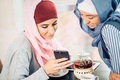 Ritratto della donna musulmana felice che per mezzo del telefono cellulare mentre sedendosi su uno strato Fotografia Stock Libera da Diritti
