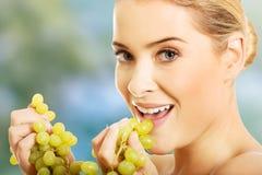 Ritratto della donna nuda che mangia l'uva Fotografie Stock Libere da Diritti